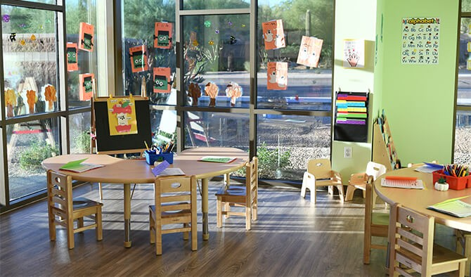 interior of classroom setting with tables, chairs, and art on the windows