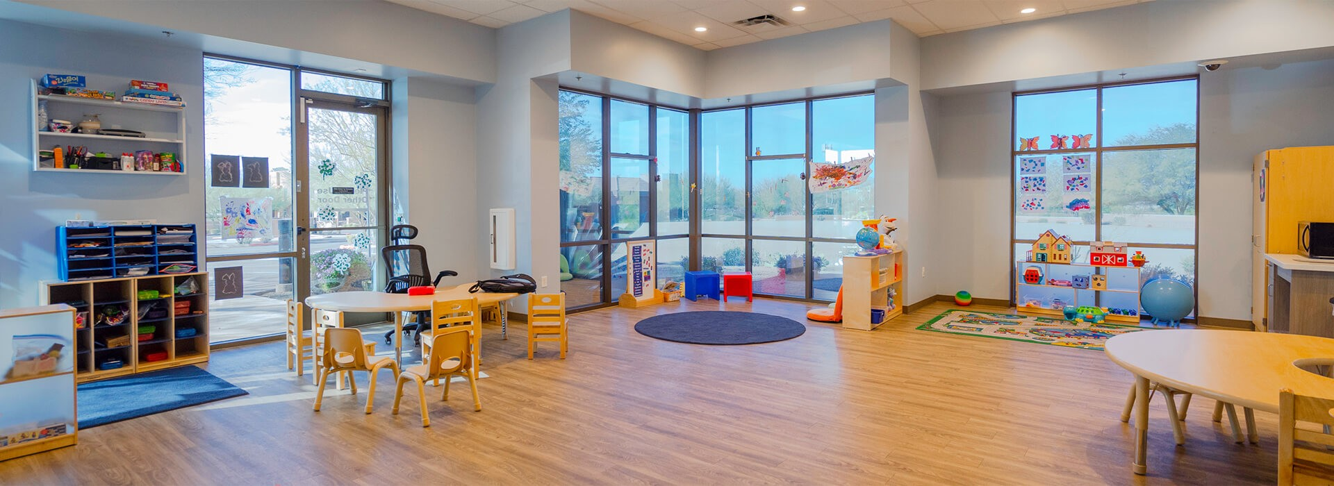 overview of a children's playroom filled with windows, tables, chairs, and toys