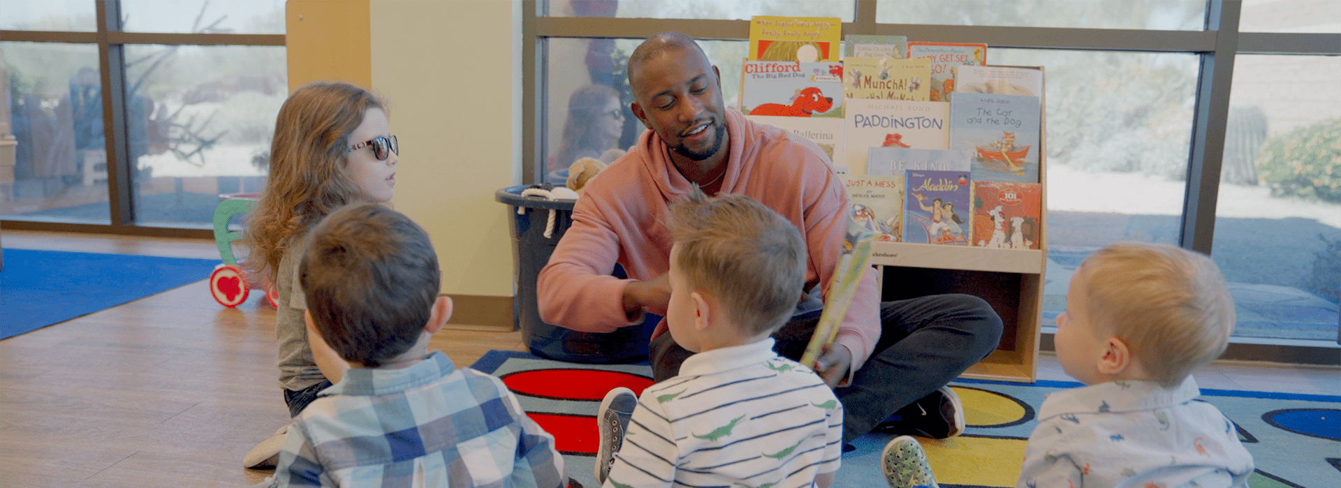 A man is surrounded by children engaged in teaching activity