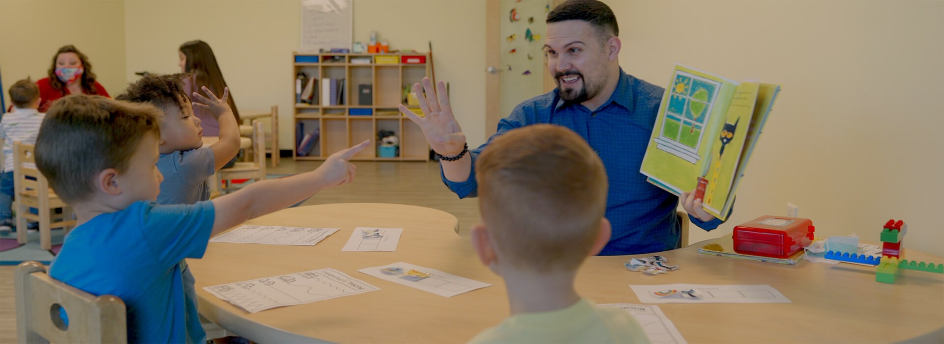 a man holds up the number 5 while holding a book while one boy is pointing at him and another is sitting