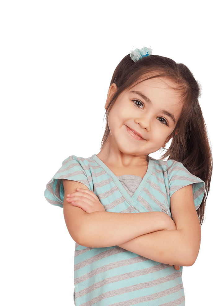 a young girl smiles with her head tiled and arms crossed